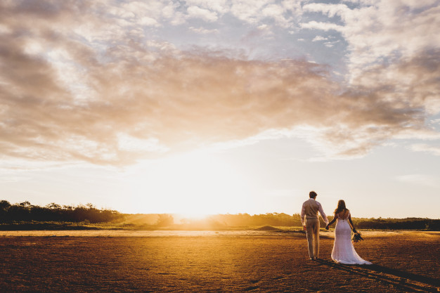 horizontal shot man woman wedding attire holding hands during sunset 181624 5025